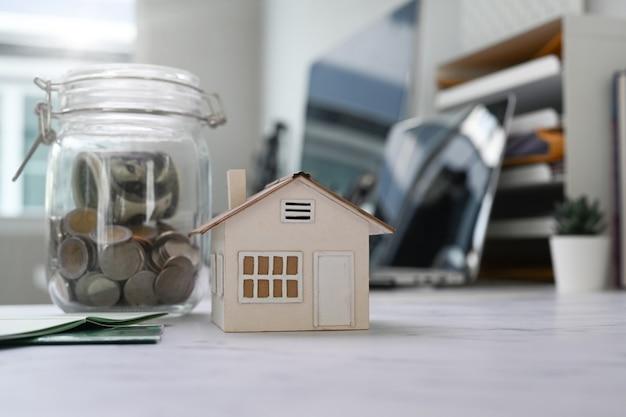 Zamknij widok szklanych słoików z monetami i model domu na stole. planowanie oszczędności na zakup domu, nieruchomości lub inwestycji w nieruchomość.