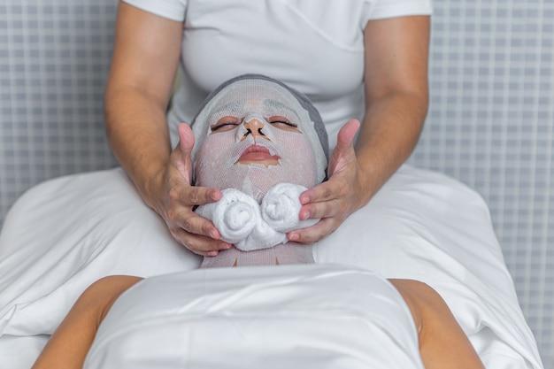 Zamknij widok terapeuty nakładający ręcznik na twarz kobiety, która jest pokryta gazą do leczenia skóry w salonie spa. koncepcja uzdrowiska.