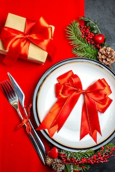 Zamknij widok tła nowego roku z czerwoną wstążką na talerz obiadowy zestaw sztućców akcesoria dekoracyjne gałęzie jodły obok prezentu na czerwonej serwetce