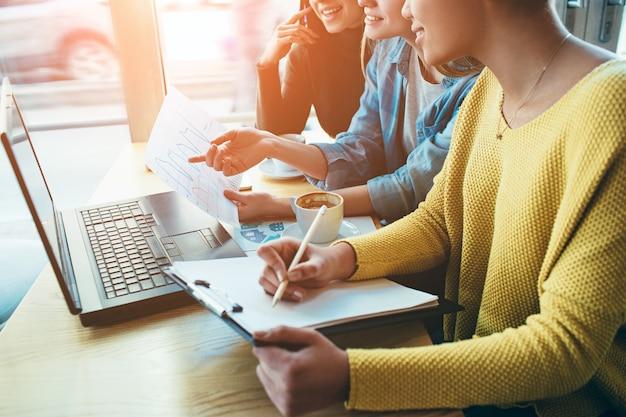 Zamknij widok trzech dziewczyn siedzących razem i studiujących wykres dochodów pieniężnych