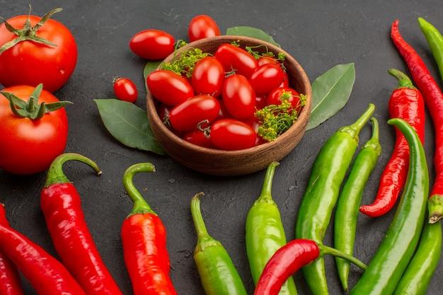 Zamknij widok u dołu miskę pomidory czereśniowe gorąca czerwona i zielona papryka pomidory i liście laurowe na czarnym tle