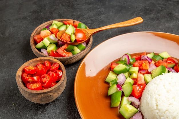 Zamknij widok wegańskiej kolacji z ryżem i różnymi rodzajami warzyw na ciemnym stole