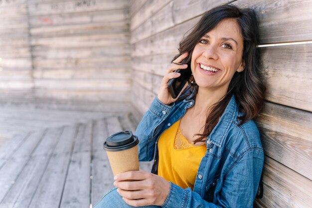 Zamknij widok wesołej kobiety łączącej dzwoniących przyjaciół i rodziny.