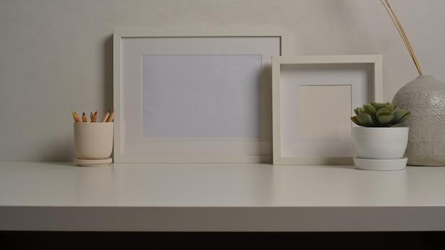 Zamknij widok wnętrz domu z makiety ramki doniczka i wazon na białym biurku