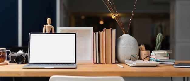 Zamknij widok wnętrza biura domowego z laptopa, książek, materiałów eksploatacyjnych i dekoracji na drewnianym stole, ścieżkę przycinającą.