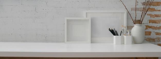 Zamknij widok współczesnego obszaru roboczego z ramkami makiety, papeterii, dekoracji i przestrzeni kopii