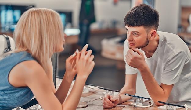 Zamknij widok z boku całkiem szczęśliwy podekscytowany hipster młoda miłość para testowania nowych inteligentnych gadżetów w sklepie tech.