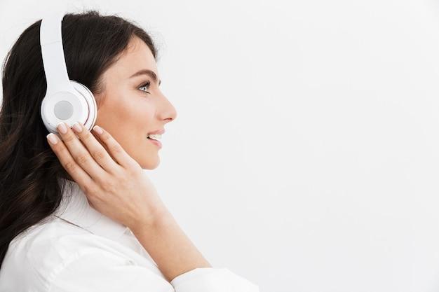 Zamknij widok z boku pięknej młodej kobiety z długimi kręconymi włosami brunetki w białej koszuli stojącej na białym tle nad białą ścianą, ciesząc się słuchaniem muzyki przez słuchawki