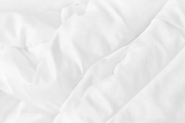Zamknij widok z góry białego prześcieradła i zmarszczki niechlujny koc w sypialni po przebudzeniu rano.