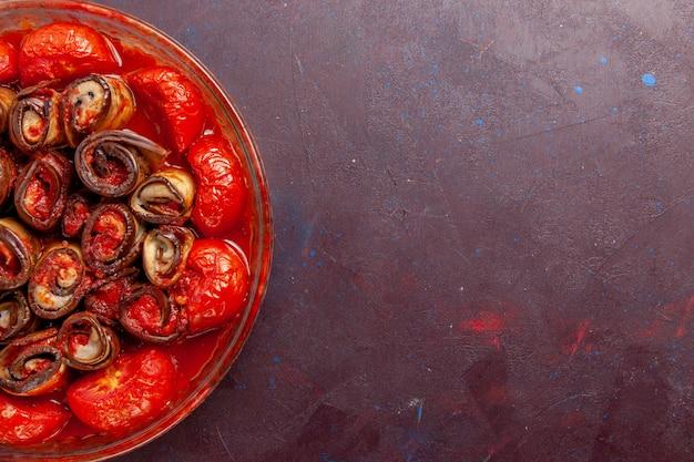 Zamknij widok z góry gotowane mączki warzywne pomidory i bakłażany na ciemnej powierzchni