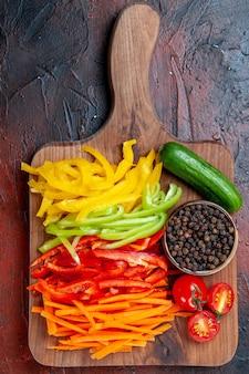 Zamknij widok z góry kolorowe papryki cięte czarny pieprz pomidory ogórek na deska do krojenia na ciemnoczerwonym stole