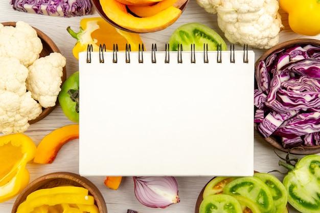 Zamknij widok z góry notatnik pokrój zielone pomidory pokrój czerwoną kapustę pokrój dyni kalafior pokrój paprykę w miseczkach na powierzchni
