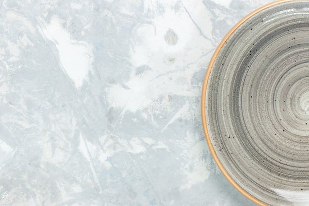 Zamknij widok z góry pusty okrągły talerz szary w kolorze białym na ścianie płyta kuchenna sztućce fotograficzne