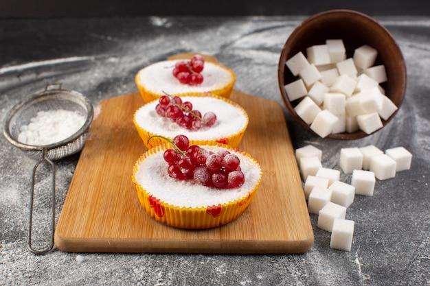 Zamknij widok z przodu ciastka żurawinowe z czerwoną żurawiną na wierzchu kawałków cukru i cukru pudru