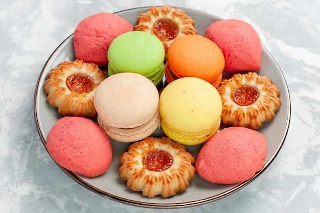 Zamknij widok z przodu francuskie makaroniki z ciasteczkami na jasnobiałej powierzchni upiec ciasto biszkoptowo-cukrowe słodkie