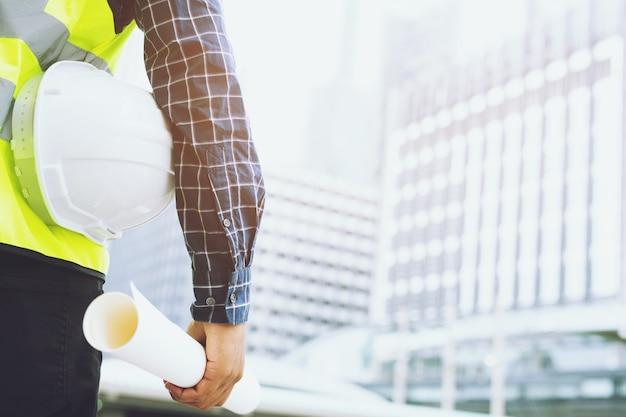 Zamknij widok z przodu inżyniera męskiego pracownika budowlanego, trzymając biały kask ochronny i nosić odzież odblaskową dla bezpieczeństwa operacji pracy.