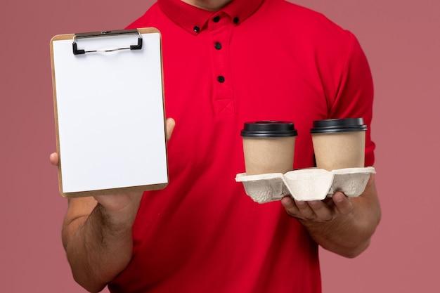 Zamknij widok z przodu kurier męski w czerwonym mundurze, trzymający brązowe kubki z kawą i notatnik na jasnoróżowym biurku