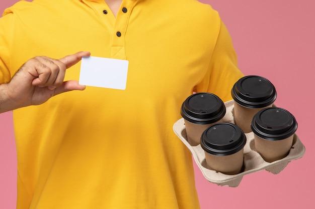 Zamknij widok z przodu kurier męski w żółtym mundurze trzymający plastikową kartę i dostawy filiżanek kawy na różowym tle