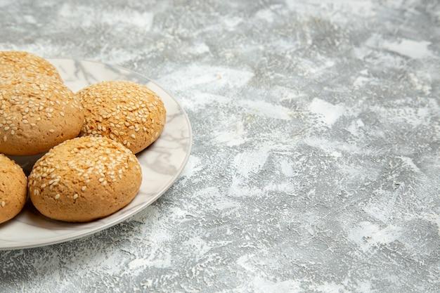Zamknij widok z przodu małe miękkie ciasteczka pyszny deser na herbatę wewnątrz płyty na białej powierzchni ciasto herbatnikowe piec cukier słodkie ciasteczko