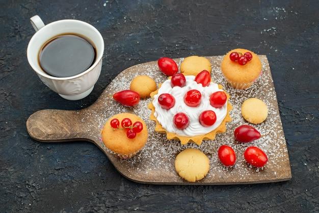 Zamknij widok z przodu małe pyszne ciasta ze śmietaną i świeżymi owocami na ciemnej powierzchni słodkie herbatniki ciasto deser owocowy