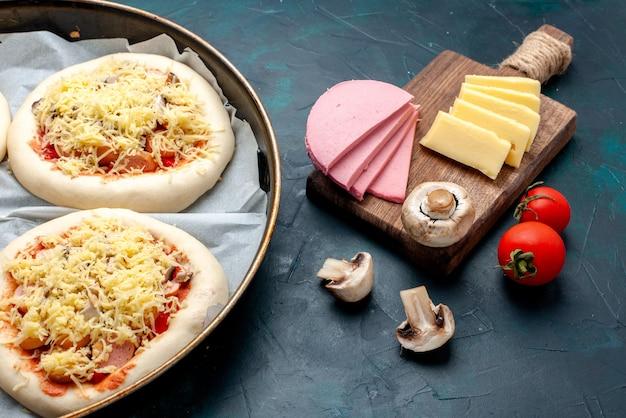 Zamknij widok z przodu małe surowe ciasto na pizzę z warzywami i serem wewnątrz patelni na ciemnoniebieskim biurku.