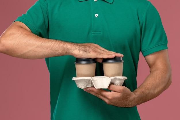 Zamknij widok z przodu mężczyzna kurier w zielonym mundurze, trzymając brązowe filiżanki kawy dostawy na różowym tle