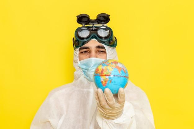 Zamknij widok z przodu mężczyzna naukowiec w specjalnym garniturze, trzymając mały okrągły glob na żółtym biurku