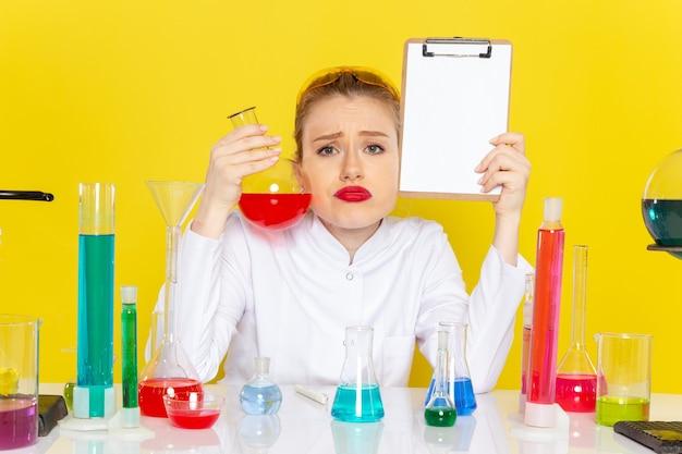 Zamknij widok z przodu młoda kobieta chemik w białym garniturze z kolorowymi roztworami pracująca z nimi i siedząca na żółtym tle