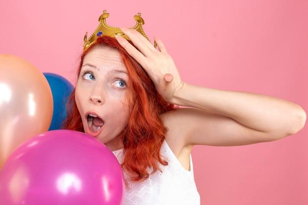 Zamknij widok z przodu młoda kobieta trzyma kolorowe balony na różowo