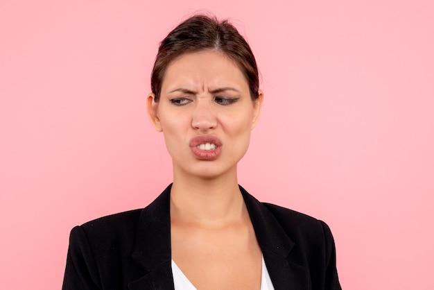 Zamknij widok z przodu młoda kobieta w ciemnej kurtce niezadowolona na różowym tle