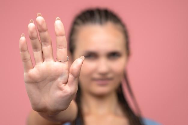 Zamknij widok z przodu młodej dziewczyny proszącej o zatrzymanie się na różowo