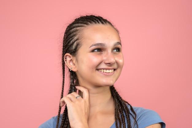 Zamknij widok z przodu młodej dziewczyny szczęśliwie uśmiechnięta na jasnoróżowym