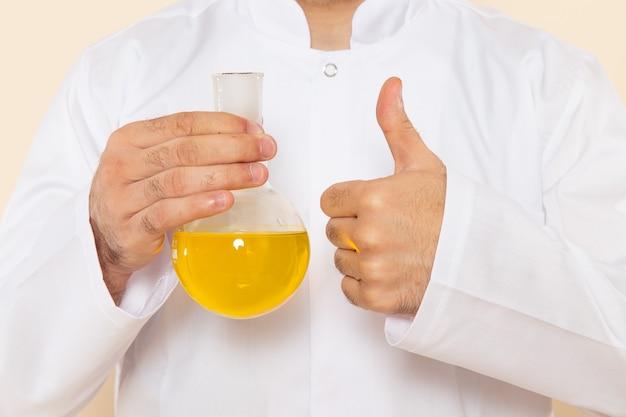 Zamknij widok z przodu młody chemik mężczyzna w białym specjalnym garniturze, trzymając kolbę z żółtym roztworem na ścianie kremu laboratorium naukowe eksperyment chemia naukowa