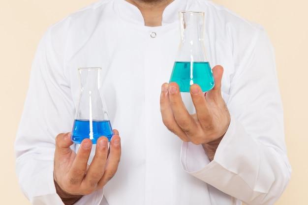 Zamknij widok z przodu młody chemik mężczyzna w białym specjalnym garniturze trzymający małe kolby z roztworami na kremowej ścianie eksperyment naukowy chemia laboratorium naukowe