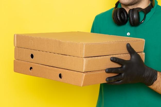 Zamknij widok z przodu młody mężczyzna kurier w zielonej koszuli, zielonej czapce, czarnych rękawiczkach, trzymających pudełka dostawy