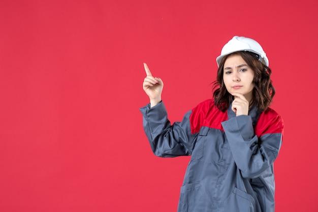 Zamknij widok z przodu myśli żeńskiej konstruktora w mundurze z kaskiem i skierowaną w górę na odizolowanej czerwonej ścianie
