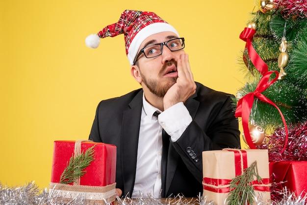 Zamknij widok z przodu pracownik płci męskiej siedzący wokół prezentów i małe drzewo myślenia na żółto