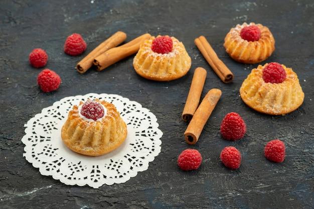 Zamknij widok z przodu pyszne ciasteczka ze świeżymi czerwonymi malinami i cynamonem na ciemnej powierzchni ciasteczka owocowe jagodowe słodkie
