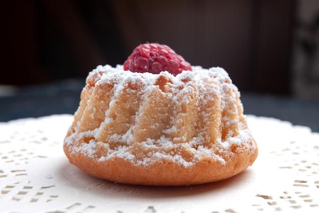Zamknij widok z przodu pyszne ciasto z kremem i czerwoną maliną na ciemnej powierzchni ciasto owocowe herbatniki cukrowe
