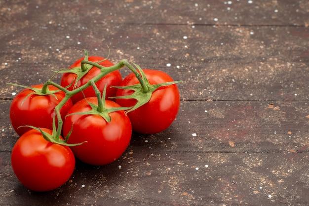 Zamknij widok z przodu świeże czerwone pomidory dojrzałe i całe na drewnianym brązowym tle kolor żywności roślinnej