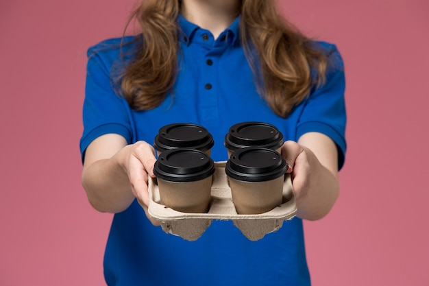 Zamknij widok z przodu żeński kurier w niebieskim mundurze dostarczający brązowe filiżanki kawy dostawy na różowym biurku jednolity pracownik firmy