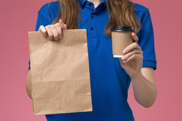 Zamknij widok z przodu żeński kurier w niebieskim mundurze, trzymając brązowy kubek kawy z pakietem żywności na jasnoróżowym biurku mundur pracy firmy dostarczającej