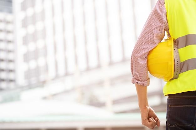 Zamknij widok z tyłu inżyniera męskiego pracownika budowlanego stojaka trzymającego żółty kask ochronny i nosić odzież odblaskową dla bezpieczeństwa operacji pracy. na zewnątrz budynku.