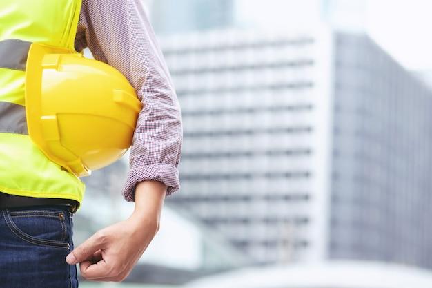 Zamknij widok z tyłu inżyniera męskiego pracownika budowlanego stojaka trzymającego żółty kask ochronny i nosić odzież odblaskową dla bezpieczeństwa operacji pracy.