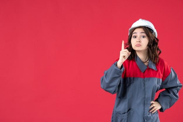 Zamknij widok zaskoczony konstruktor kobiet w mundurze z kaskiem i skierowaną w górę na odosobnionej czerwonej ścianie