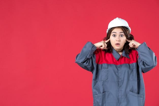 Zamknij widok zaskoczony konstruktor kobiet w mundurze z kaskiem i zamykając uszy na izolowanej czerwonej ścianie