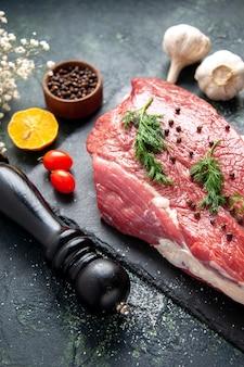 Zamknij widok zieleni na świeżym czerwonym surowym mięsie na desce do krojenia i pieprzu cytryna czarny młotek kwiat na zielonym czarnym mieszanym kolorze tła