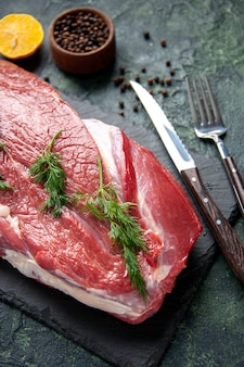 Zamknij widok zieleni na sztućce świeżego czerwonego surowego mięsa na desce do krojenia i cytryny pieprzowej na zielonym czarnym mieszanym kolorze tła