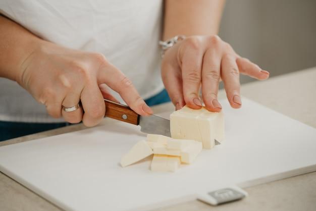 Ð zamknij zdjęcie dłoni młodej kobiety, która ostrym nożem kroi świeże masło na desce do krojenia.