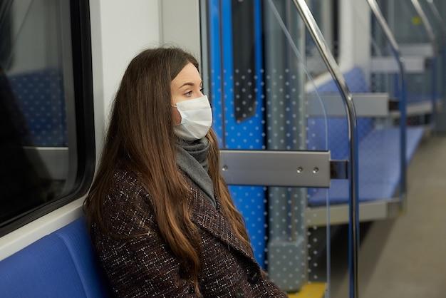 Zamknij zdjęcie kobiety w masce medycznej siedzącej samotnie w nowoczesnym wagonie metra